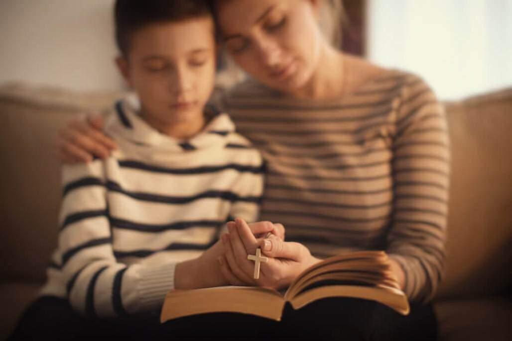 mãe e filho rezando (shutterstock)