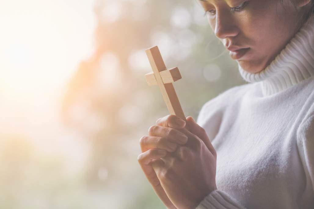 Mulher segurando a cruz, conversão, aceitar Jesus, escolher seguir Jesus (Tinnakorn jorruang/ Shutterstock)